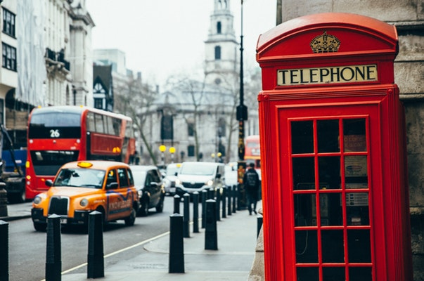 Telephone booth on the street with cars