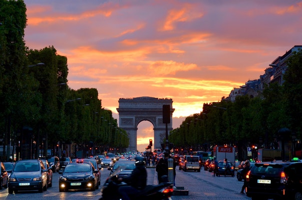 cars and the paris monument as backdrop with the sunseting